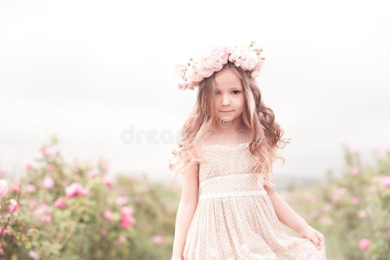 Barnflicka som poserar i rosträdgård royaltyfria bilder