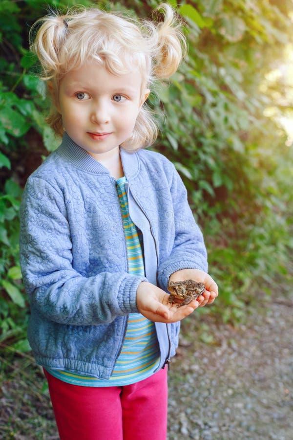 barnflicka som rymmer den lilla skoggrodapaddan arkivfoto