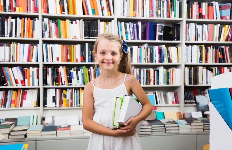 Barnflicka som rymmer en bunt av böcker i en bokhandel royaltyfria foton