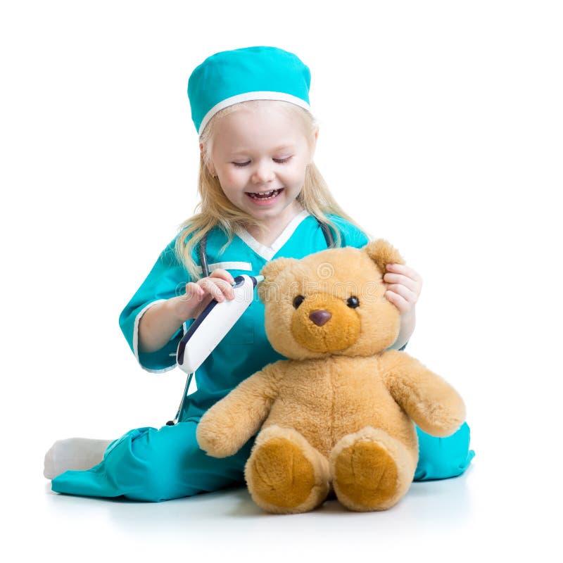 Barnflicka som spelar doktorn med den flotta leksaken arkivbilder