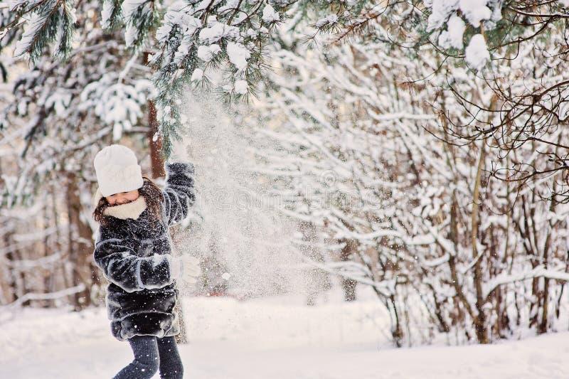 Barnflicka som spelar med den insnöade vinterskogen royaltyfri foto