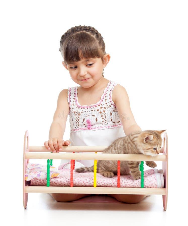 Barnflicka som spelar med kattkattungen och vaggar honom i dockalathund fotografering för bildbyråer