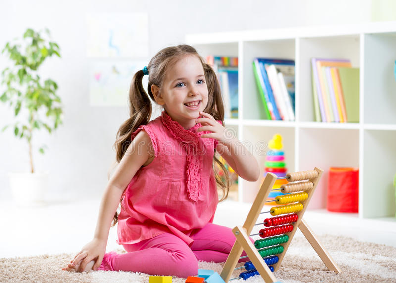 Barnflicka som spelar med kulrammet fotografering för bildbyråer