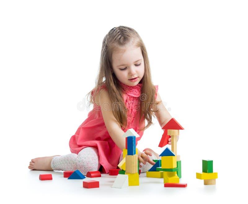 Barnflicka som spelar med kvarterleksaken royaltyfri bild