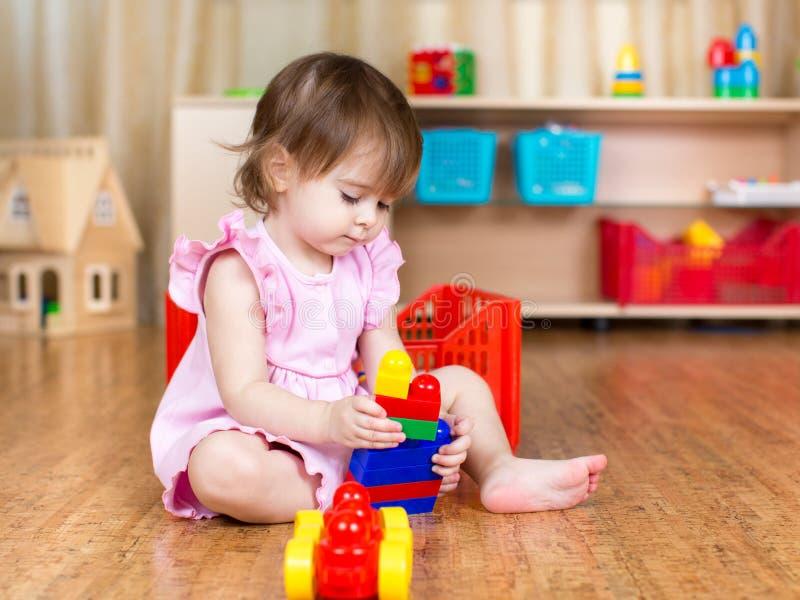 Barnflicka som spelar med kvarterleksaker inomhus arkivfoton