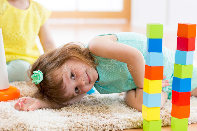 Barnflicka som spelar med kvarterleksaker på golv royaltyfri fotografi