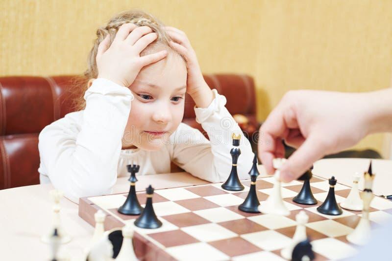 Barnflicka som spelar schackleken arkivbild