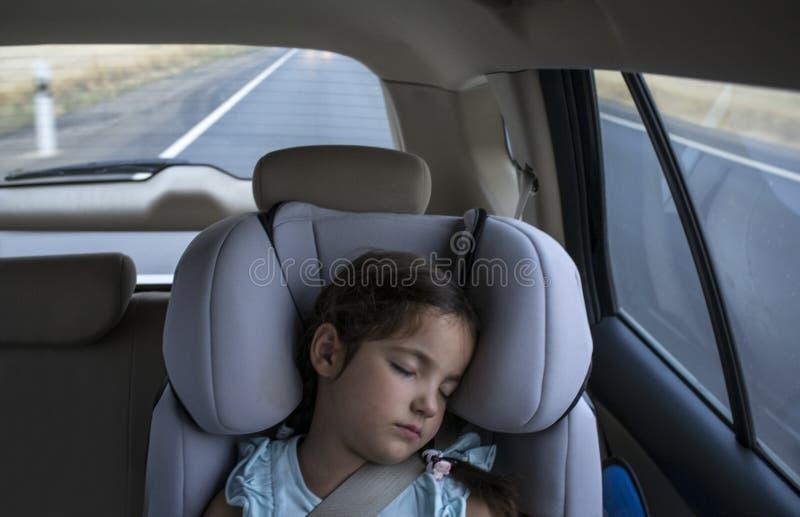 Barnflicka sovande i en barnsäkerhetsplats i en bil fotografering för bildbyråer