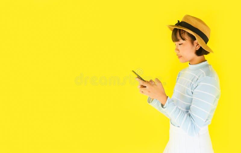 Barnflickahänder som rymmer smartphonen på gul bakgrund - asiatisk ung kvinna som använder nätt mobiltelefonmode i sommaren och royaltyfria bilder