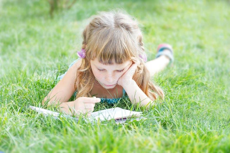 barnflickaläsebok utomhus på naturlig bakgrund fotografering för bildbyråer