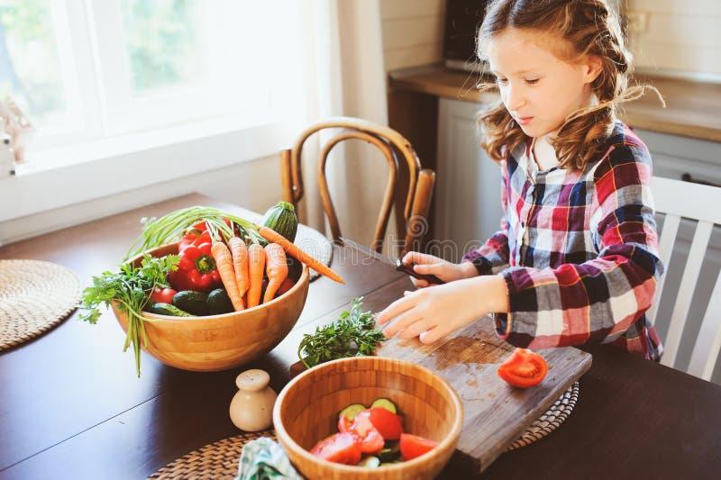 Barnflickan hjälper mamman att laga mat och klippa nya grönsaker för sallad med kniven royaltyfri bild