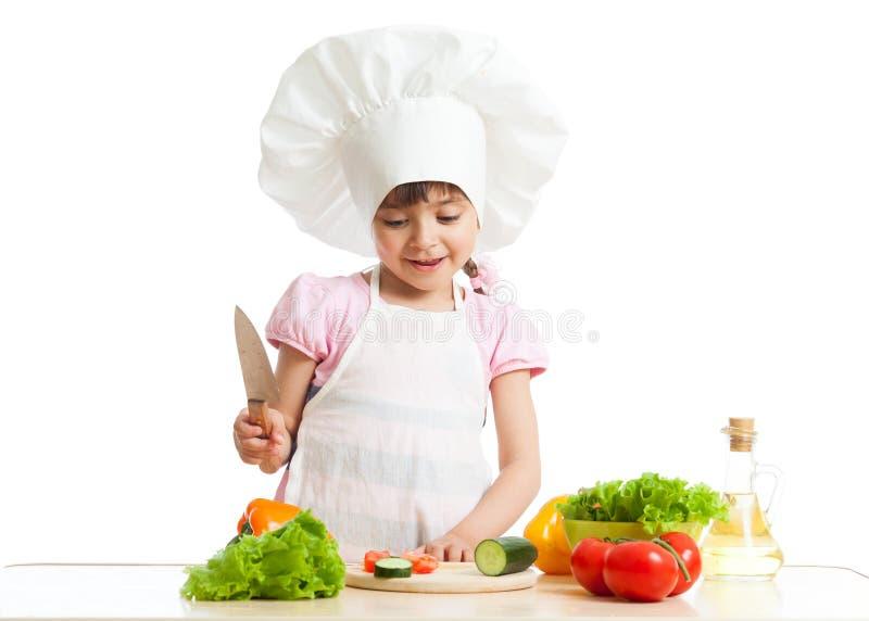 Barnflickan klipper grönsaker för sallad genom att använda kökkniven som isoleras över vit arkivfoton