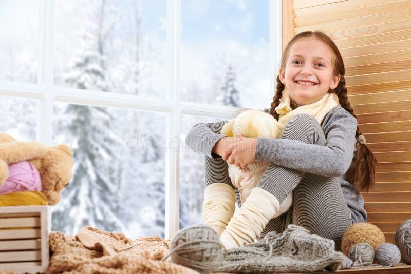 Barnflickan sitter på en fönsterfönsterbräda och spelar med björnleksaken Härlig sikt utanför fönstret - solig dag i vinter och s arkivfoton