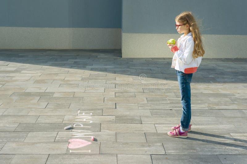 Barnflickan skrev på asfalten jag älskar mitt planet Äter ett äpple och ser texten, den sunda livsstilen, sunt äta arkivfoto