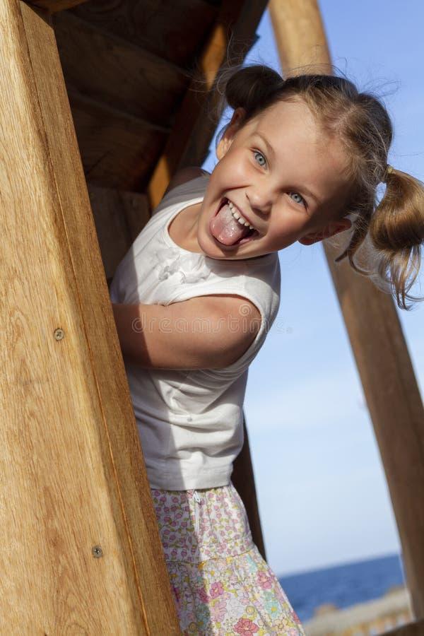 Barnflickan som spelar i lekplatsen parkerar in arkivbilder