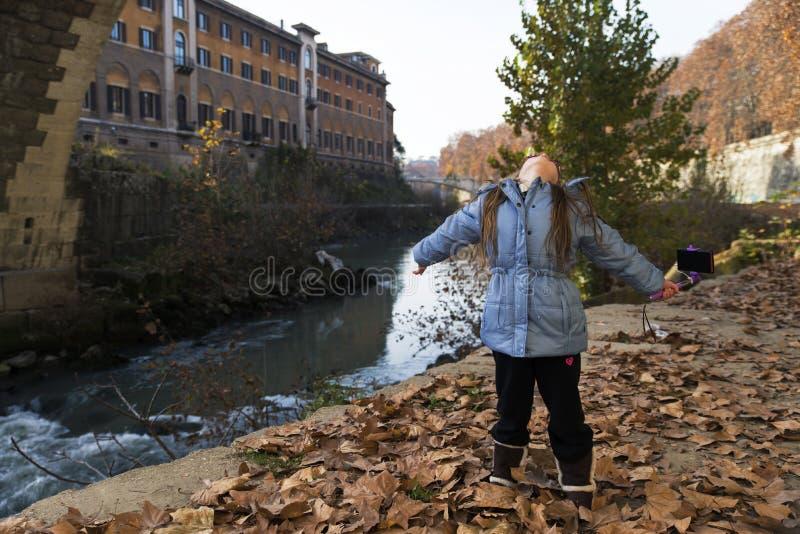 Barnflickasammanträde på den soliga höstflodstranden royaltyfri fotografi