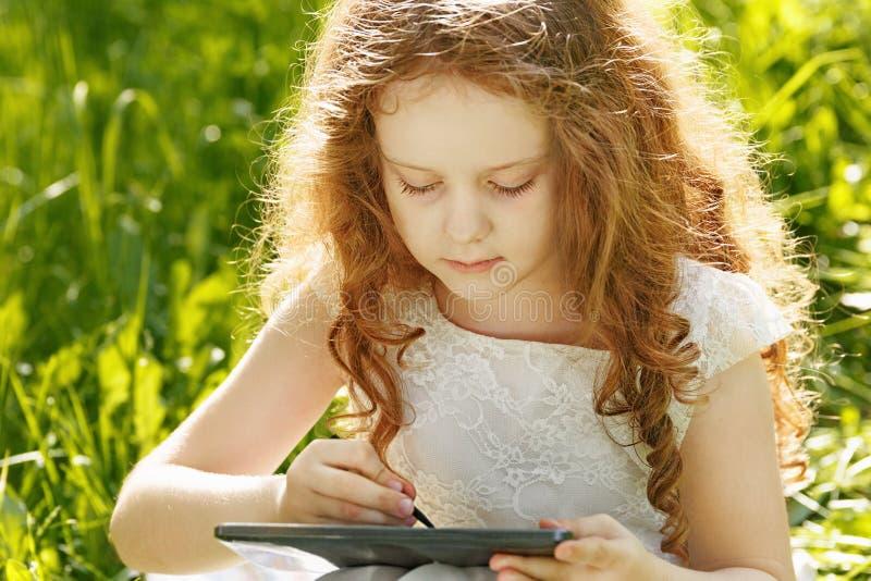 Barnflickasammanträde på gräs och spela minnestavlaPC arkivbild