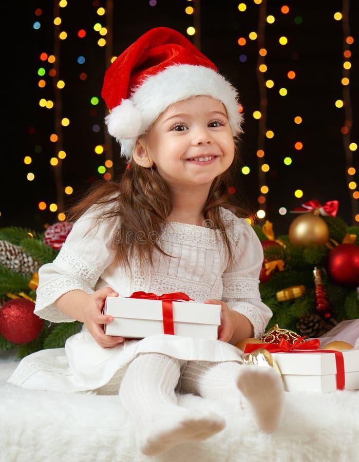 Barnflickastående i julgarnering, lyckliga sinnesrörelser, begrepp för vinterferie, mörk bakgrund med belysning och bokeli royaltyfri bild