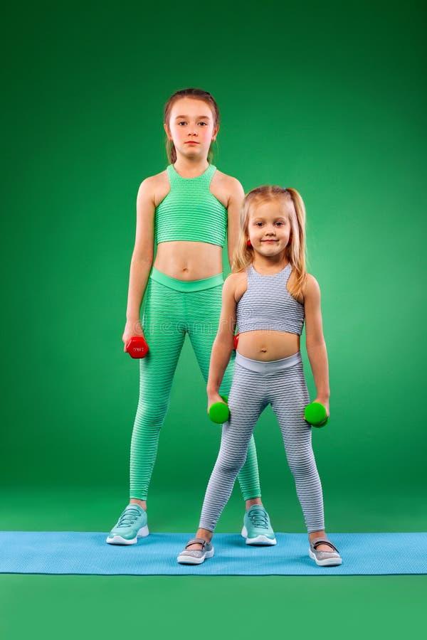 Barnflickor som gör kondition, övar på grön bakgrund tillsammans arkivbild