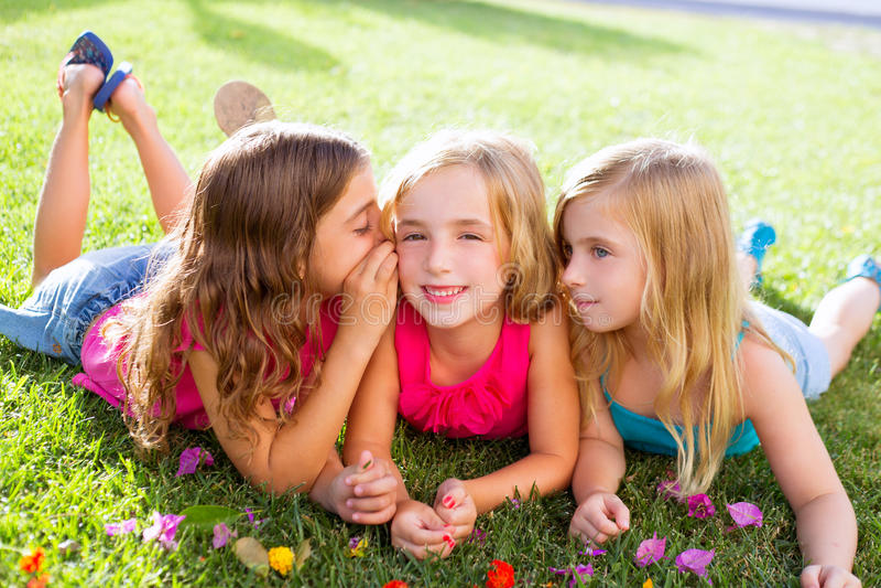 Barnflickor som leker att viska på blommagräs fotografering för bildbyråer