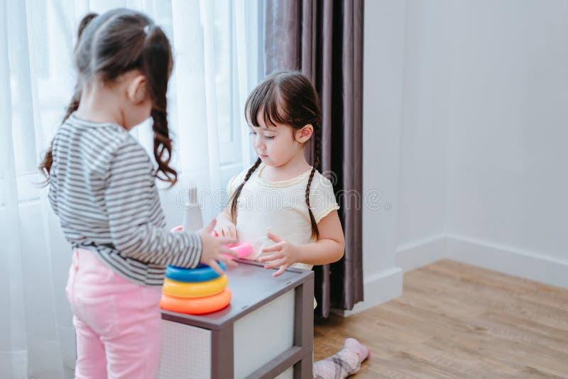 Barnflickor spelar en leksak spelar i rummet arkivbild