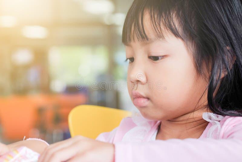 Barnflickor spelar leksaker framme av henne fast beslutsamt royaltyfri bild