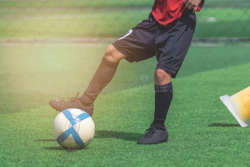 Barnfot som dreglar och trycker på fotbollbollen på ett fält royaltyfri fotografi
