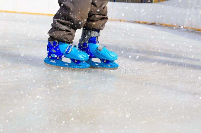 Barnfot som lär att åka skridskor på is i vinter royaltyfria bilder