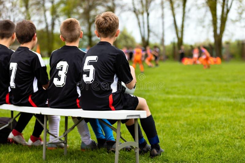Barnfotbolllag på en bänk Ung fotboll Team Players Young Boys i svarta skjortor som spelare för en ersättningfotboll fotografering för bildbyråer