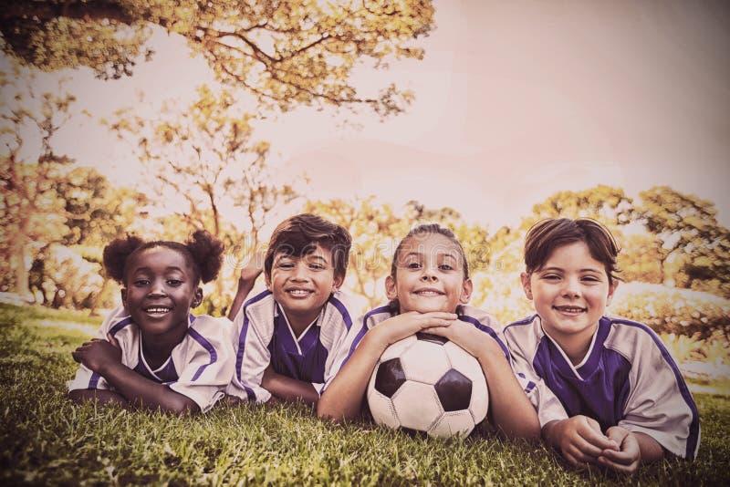 barnfotbolllag som ler på kameran, medan ligga på gräset arkivfoton