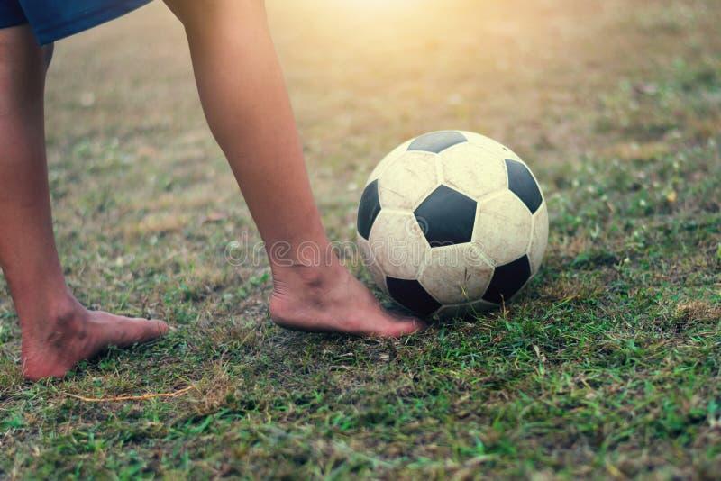 barnfoten för selektiv fokus spelar och fotbollbollen arkivbild