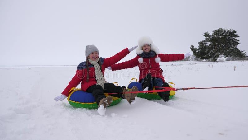 Barnglidbanor i snö på ett uppblåsbart snörör och vågor räcker Lyckliga flickaglidbanor till och med snö på släden Leka för ungar arkivfoto