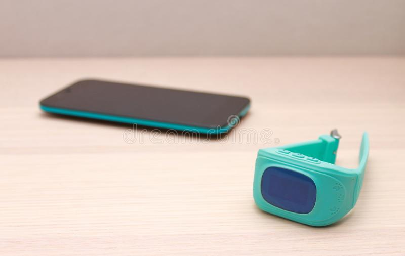 BarnGPS klocka och en smart telefon på träskrivbordet arkivfoton