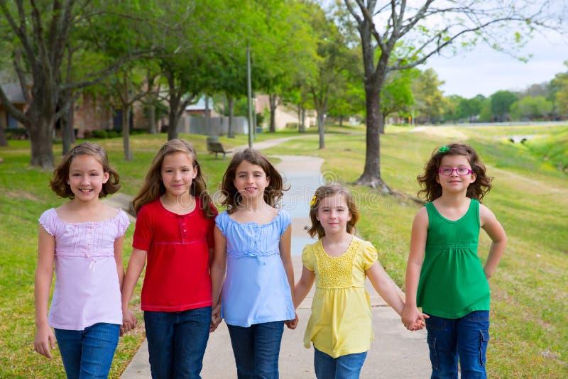 Barngruppen av systerflickor och vänner som in går, parkerar arkivfoto