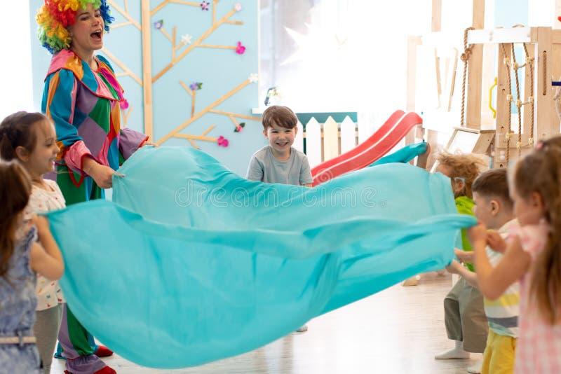 Barngruppen har gyckel på partiet Clownen underhåller ungar royaltyfria foton