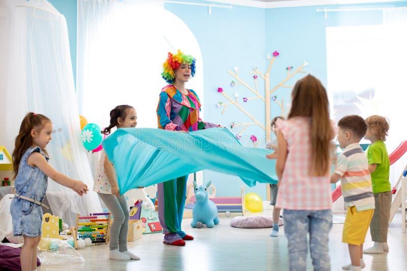 Barngruppen har gyckel p? partiet Clownen underh?ller ungar royaltyfri foto