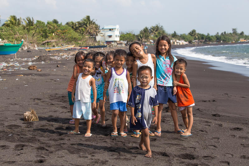 Barngruppstående på stranden med vulkanisk sand nära den Mayon vulkan, Filippinerna royaltyfri fotografi