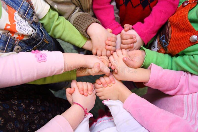 barnhänder som har sammanfogat övre sikt för stand arkivfoto