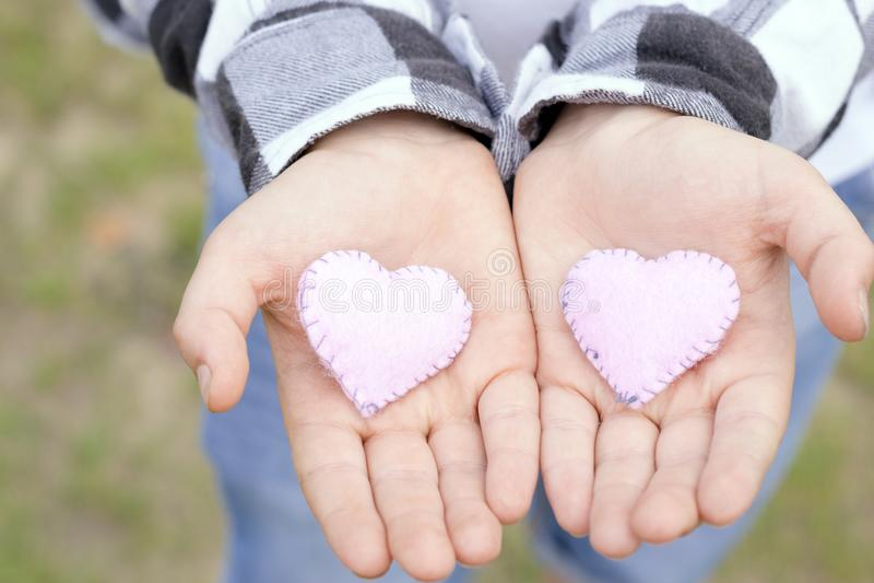 Barnhänder som rymmer handgjorda hjärtor royaltyfria foton