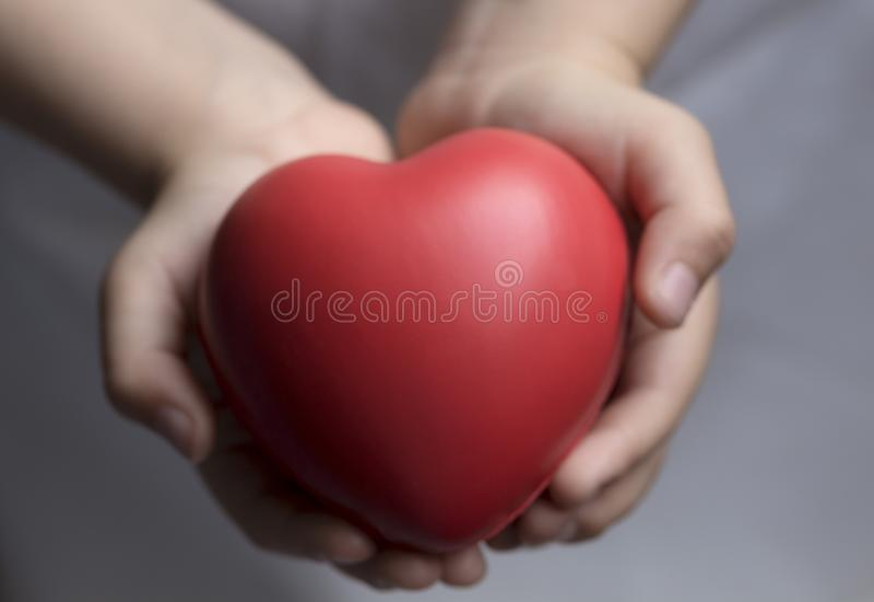 barnhänder som rymmer röd hjärta, hälsovård, donerar och familjförsäkringbegreppet, världshjärtadagen, dagen för världshälsa, CSR royaltyfri fotografi