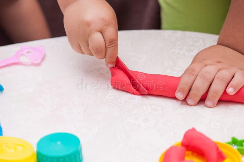 Barnhänder som spelar med färgrik lera Barnlek med plasticine royaltyfria foton