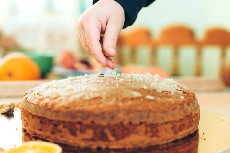 Barnhänder strilar den hemlagade kakan Baka den läckra pajen i köket Sund och hemlagad kaka royaltyfria foton