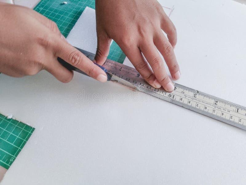 Barnhanden klipper skumpapperet med en sk?rarekniv royaltyfri fotografi