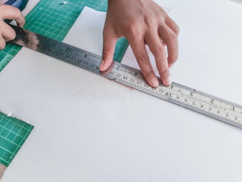Barnhanden klipper skumpapperet med en sk?rarekniv arkivfoton