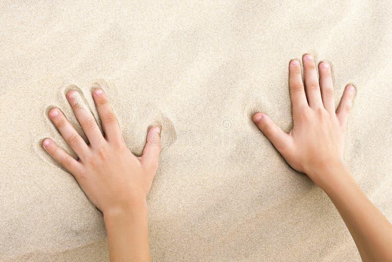 Barnhandlag av guld- sand på stranden arkivbild