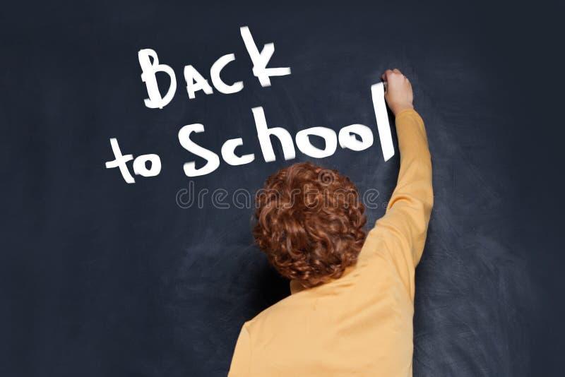 Barnhandstilpojke tillbaka till skolatext på svart tavlabakgrund arkivbild
