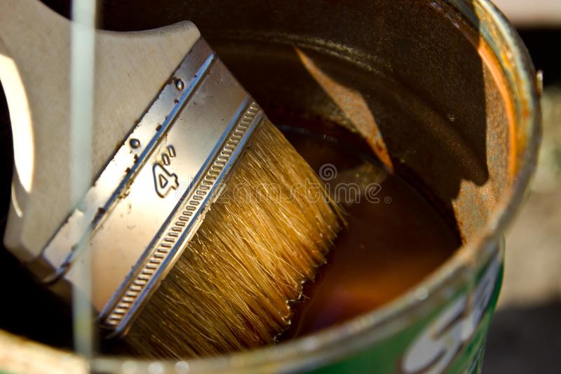 Barniz y x28; stain& x29; para cubrir la madera y el cepillo imagenes de archivo