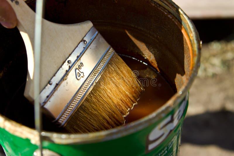 Barniz y x28; stain& x29; para cubrir la madera y el cepillo fotos de archivo