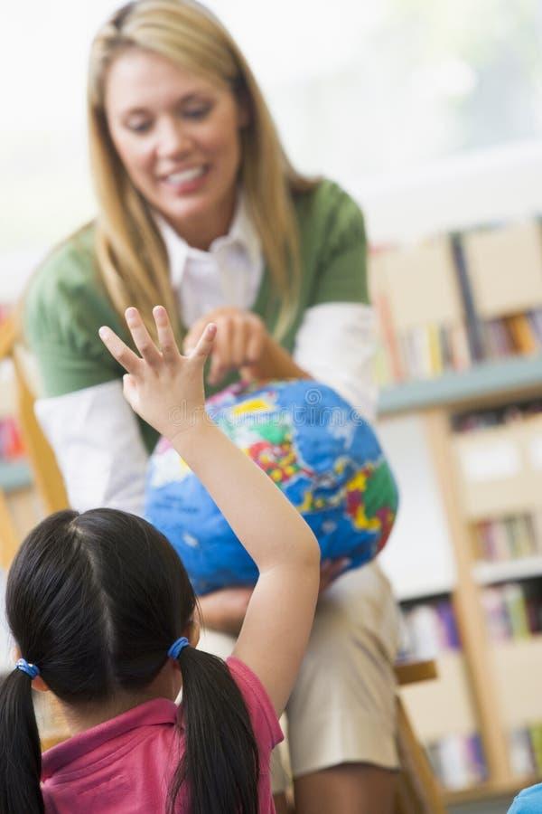 barnjordklotdagis som ser lärare arkivfoton