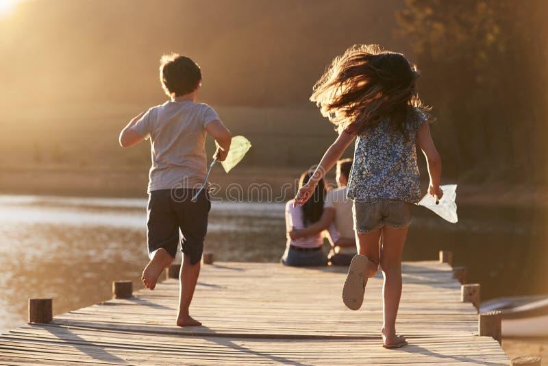 Barnkörning in mot föräldrar på träbryggan vid sjön royaltyfri bild